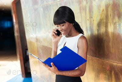 Businesswoman reading papers and talking on the phone