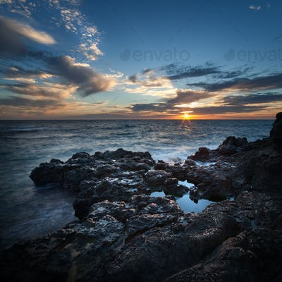 Sea coast under blue sky with clouds at sunset