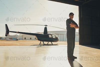Confident pilot standing in airplane hangar