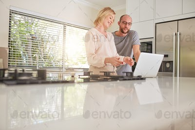 Happy couple using laptop in the kitchen at home