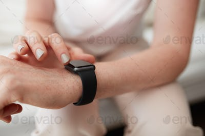 Woman checking time on her smart watch