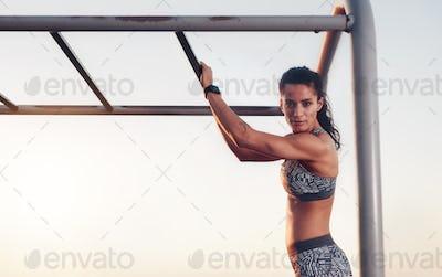 Fitness woman training outdoors on monkey bars