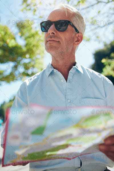 Mature tourist with a city map