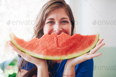 Happy young woman holding a slice of watermelon