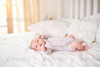 Little baby boy lying on bed in onesie, white bedroom