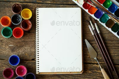 Paper, watercolors and paint brush on wooden background
