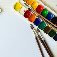 Watercolors and paint brush on white wooden background