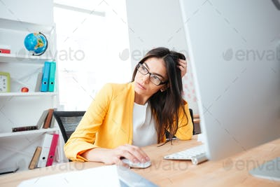 Businesswoman sitting at the table with computer in office