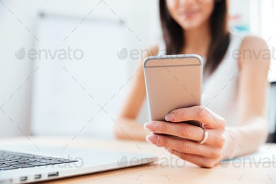 Female hands using smartphone in office