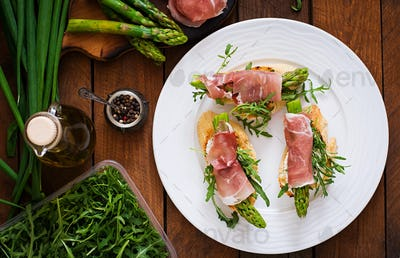 Toasts (sandwich) with asparagus, arugula and prosciutto. Top view