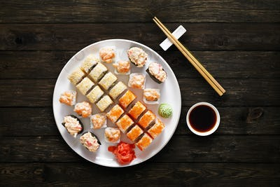 Set of sushi maki and rolls at black background