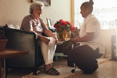 Female nurse visiting senior patient for checking blood pressure