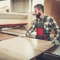 Carpenter works on wood plank in carpentry workshop.