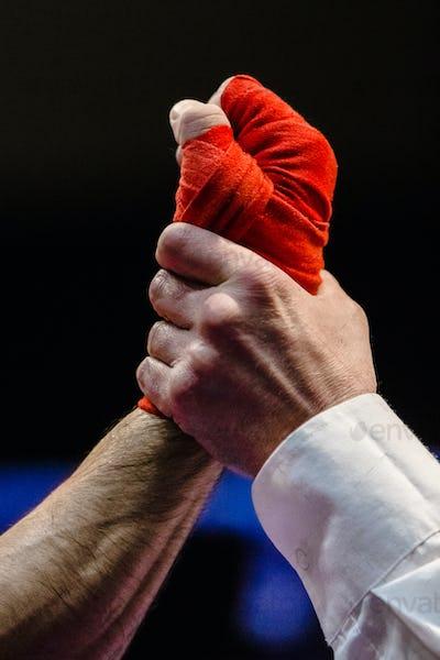 referee raises  hand of  boxer is winner