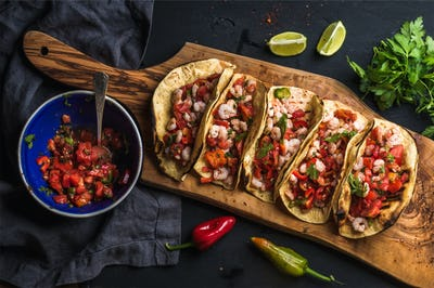 Shrimp tacos with homemade salsa, limes and parsley