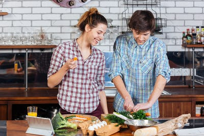 Beautiful couple standing and cooking together on kitchen