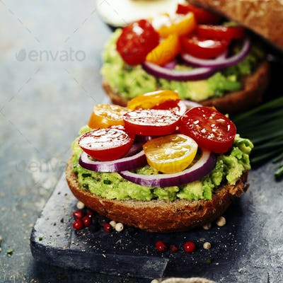 Tasty homemade sandwiches with avocado, tomato, onion and pepper
