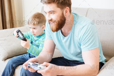 Little boy playing video games with dad sitting on sofa