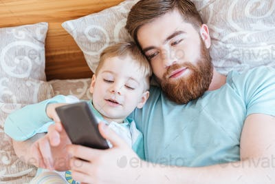 Father lying on bed with son and using mobile phone