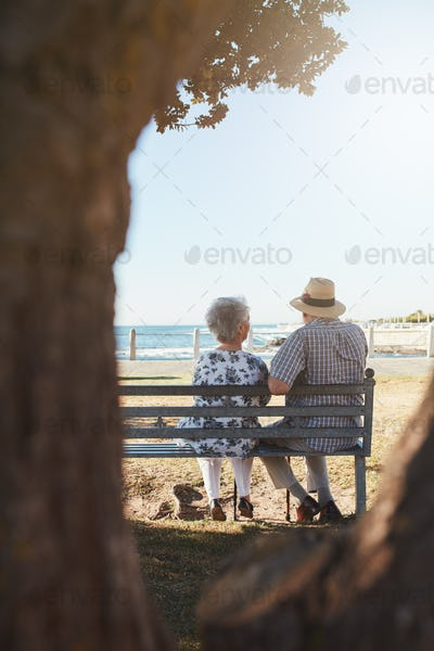 Senior couple sitting on bench near the sea