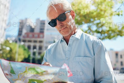 Mature tourist consulting a map while touring a foreign city