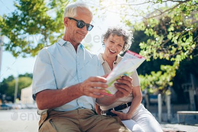 Mature couple sitting outdoors with a city map