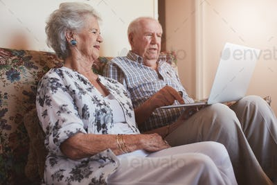 Senior couple sitting on a couch with a laptop