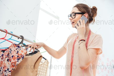 Happy woman fashion designer with measuring tape using cell phone