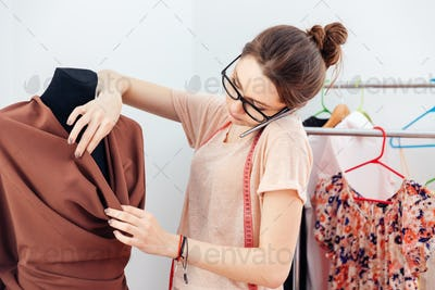 Concentrated woman fashion designer talking on cell phone
