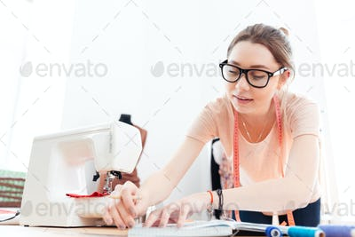 Concentrated woman seamstress wearing glasses standing and working in workshop