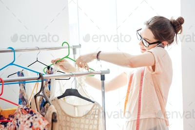 Smiling woman fashion designer talking on cell phone