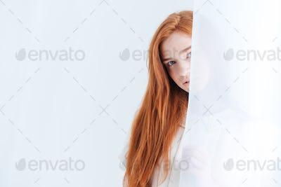 Woman peeking from curtain
