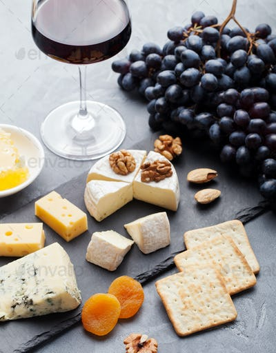 Assortment of cheese with honey, nuts and grape on a modern cutting board slate background.