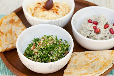 Assortment of dips: hummus, chickpea dip, tabbouleh salad, baba ganoush and flat bread, pita on a
