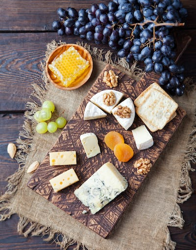 Assortment of cheese with honey, nuts and grape