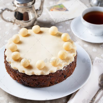 Traditional English Easter cake with marzipan decoration on a white plate.