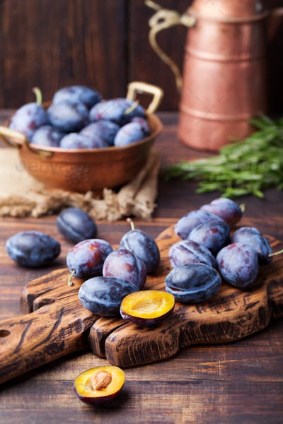 Fresh organic plums in copper bowl and on rustic wooden cutting board.