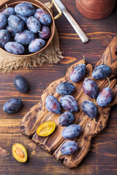 Fresh organic plums in copper bowl and on rustic wooden cutting board Top view