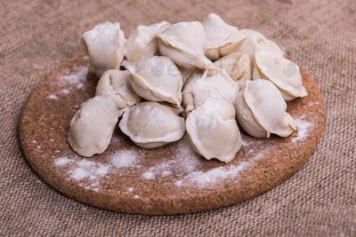 Uncooked dumplings Pelmeni. Traditional Russian dish. Background from pelmeni laid out on a chopping