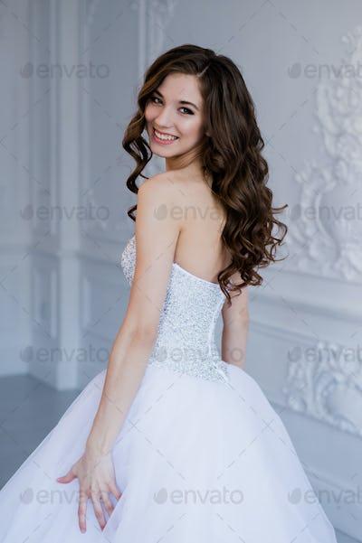 portrait of happy beautiful bride against luxury light background