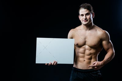 Shirtless muscular young man standing holding a blank horizontal white banner pointing finger at the