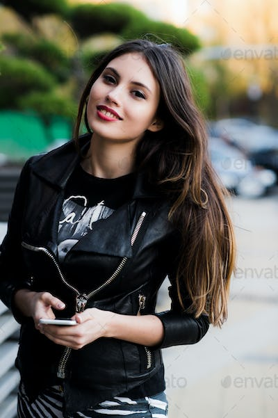 Girl walking and texting on the smart phone in the street wearing a leather jacket in summer