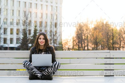 Student sitting on bench listening to music and using laptop against university campus