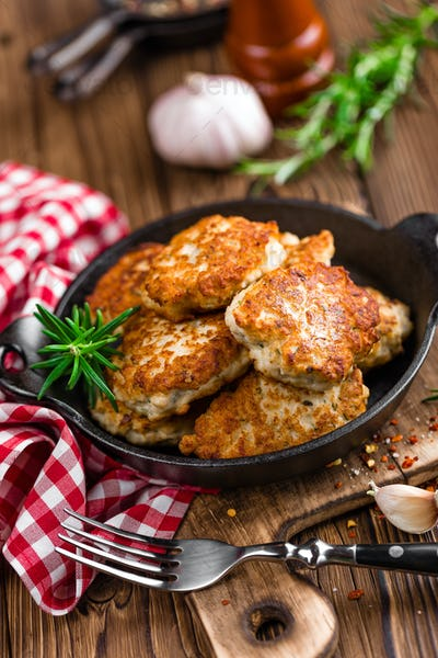 meat cutlets in frying pan on wooden rustic table