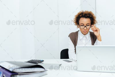 Concentrated african american woman accountant working in office using laptop