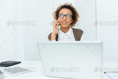 Smiling african american woman accountant talking on cell phone