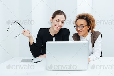 Two smiling businesswomen sitting at table and using laptop together