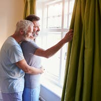 Male couple embrace looking out of their hotel room window