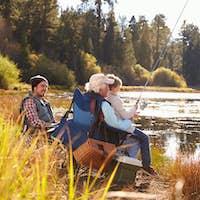 Grandad teaches his grandson to fish at a lake, dad watching