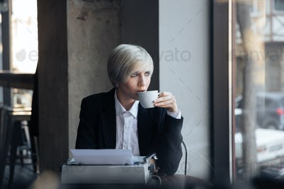 Beautiful blonde girl drinking coffee in modern cafe